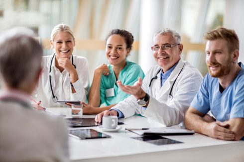 Group of happy doctors communicating on a meeting in the hospital.