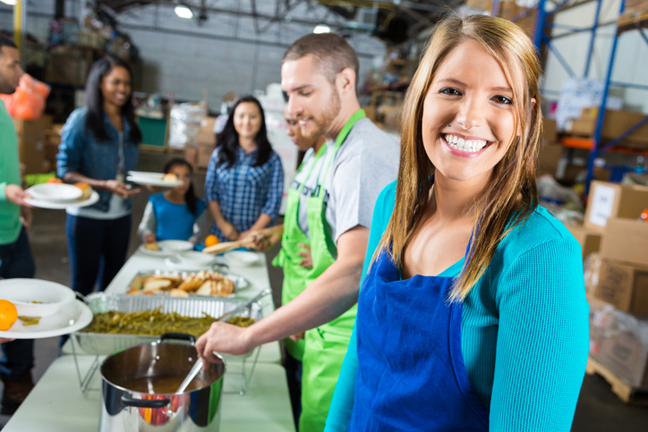 mid-adult Caucasian female volunteer serves food at local food kitchen. Volunteers are serving people in line in the background. The woman has long brown hair and is wearing a blue apron.