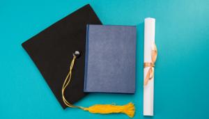 graduation cap, book, and diploma