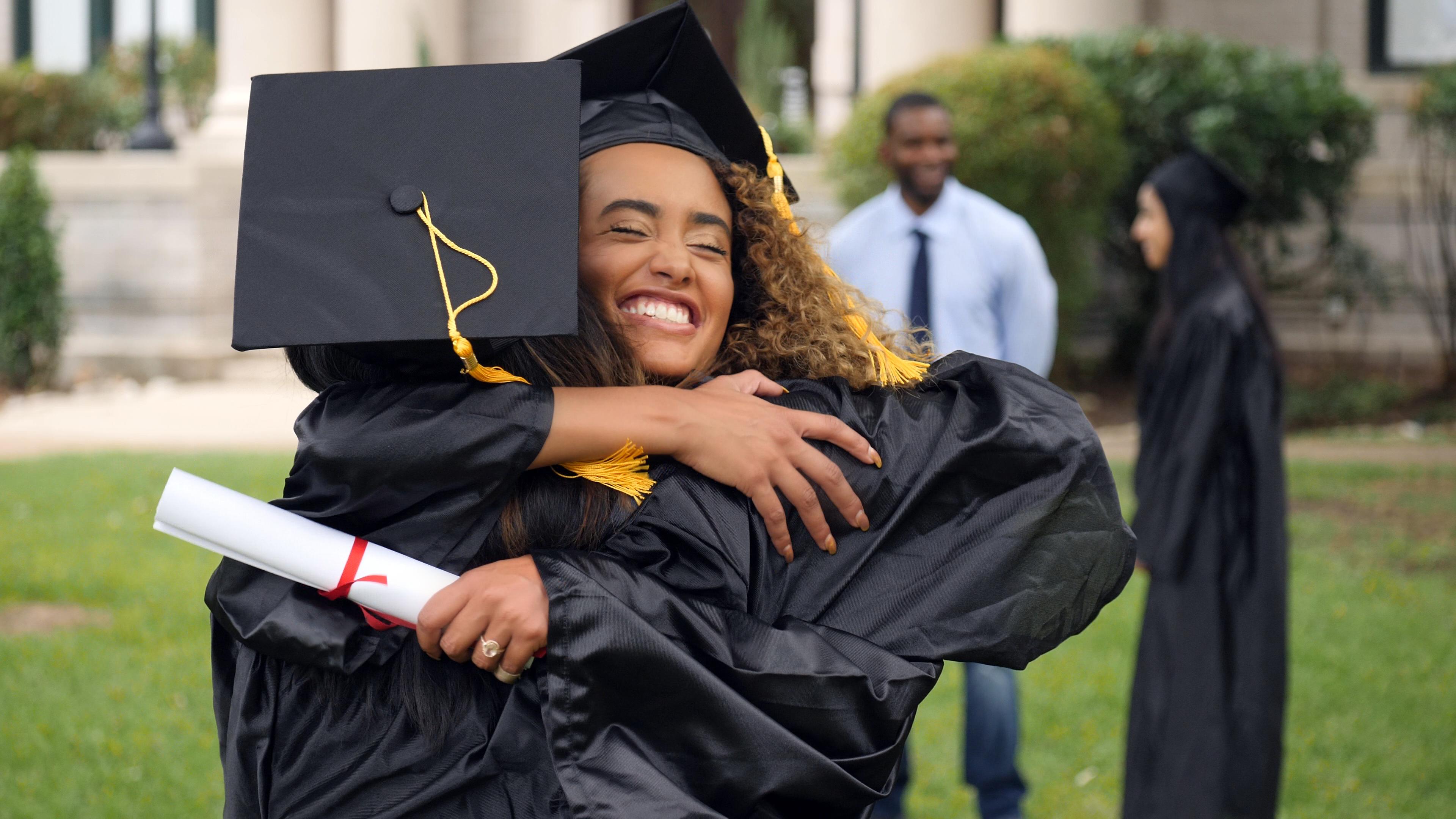 graduate hugging a classmate