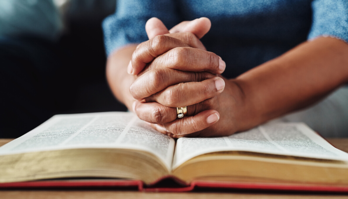woman's hands folded on the bible