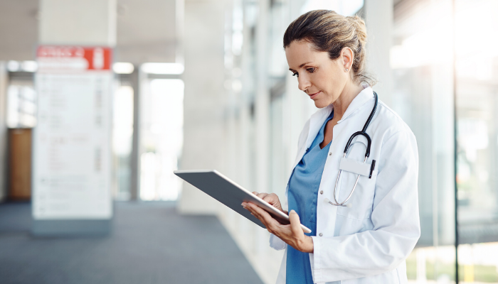 woman nurse practitioner charting on tablet