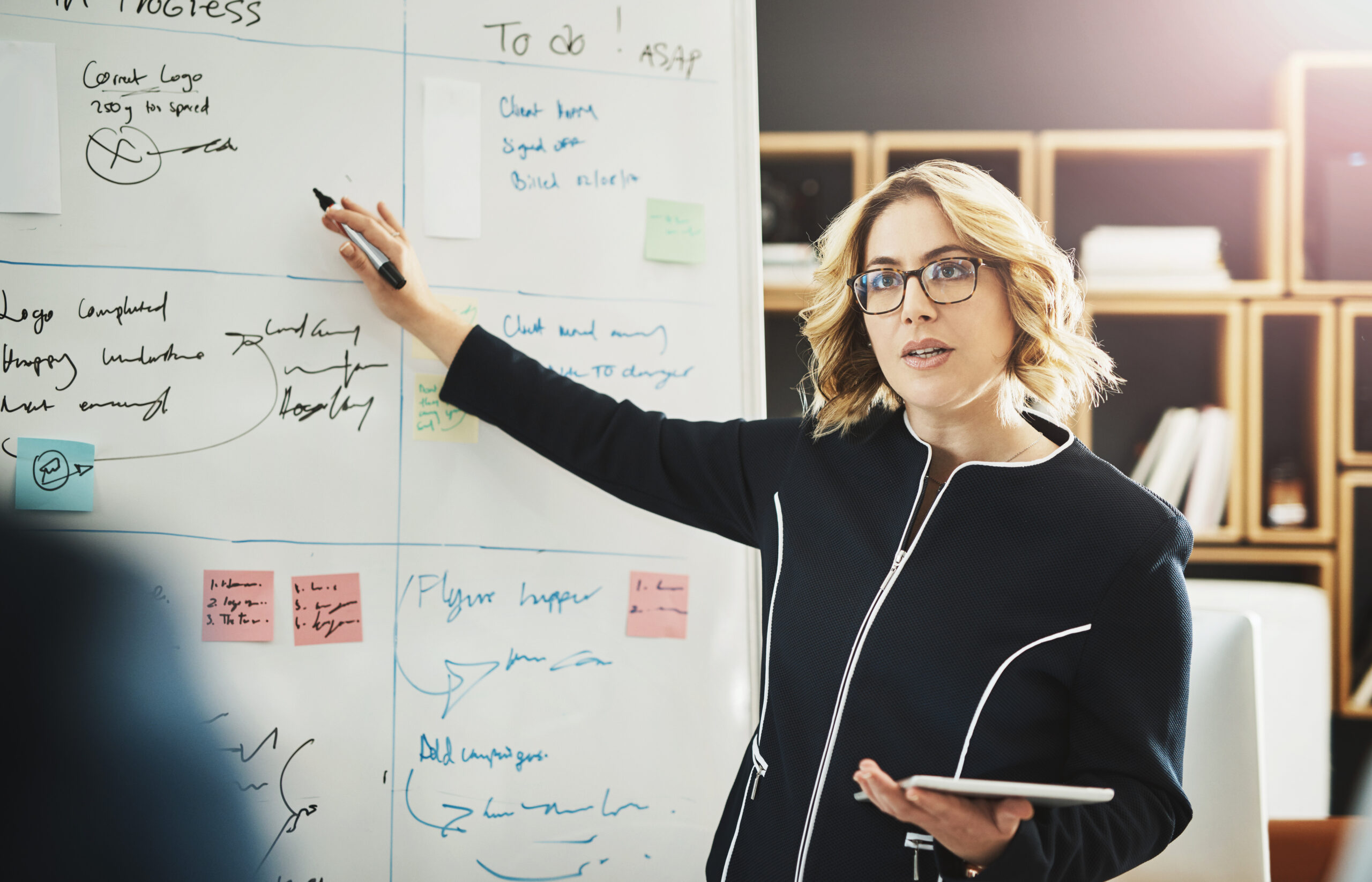 Woman pointing to white board leading a meeting