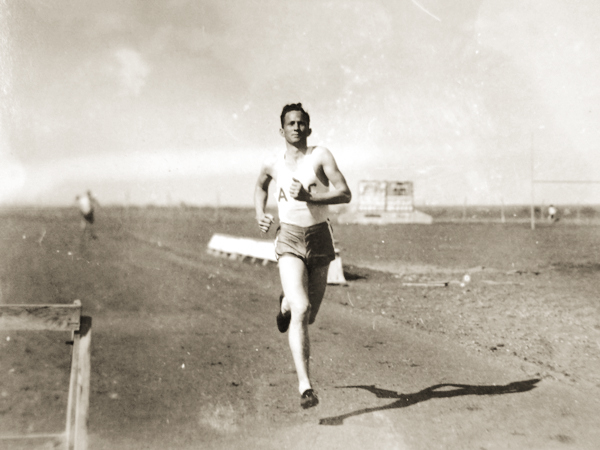 Elmer Womack ('41) sprints on the dirt track at old A.B. Morris Stadium, the forerunner of Elmer Gray Stadium. The Wildcat track and field and football teams used the facility, which is approximately where today's Mabee Business Building is located.