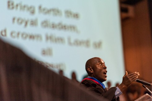 """Dr. Odies Wright Jr. ('73), associate professor of kinesiology and nutrition, leads the singing of """"All Hail the Power of Jesus' Name"""" during the Opening Assembly devotional."""