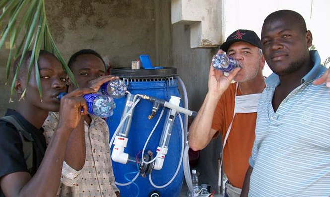 Global Samaritan Resources' water purification effort in Haiti following the 2010 earthquake is similar to the one that will be used to combat Ebola in West Africa. Here, GSR trustee Dr. Ben Gray, is pictured with Haitians drinking water purified of cholera and other diseases.
