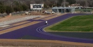 A worker paints lane lines onto the stadium's running surface last month. This image was taken from the live webcam atop Edwards Hall.