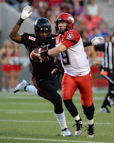 Ottawa Redblacks' Aston Whiteside moves in to knock the ball from the hand of Calgary Stampeders' Bo Levi Mitchell during second quarter CFL football action in Ottawa on Friday, July 24, 2015. Whiteside gained possession of the ball to make an interception. THE CANADIAN PRESS/Sean Kilpatrick