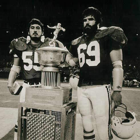 Senior linebackers Ray Nunez (55) and John Usrey (69) pose with the trophy for ACU's last national title in football, won at the 1977 Apple Bowl.