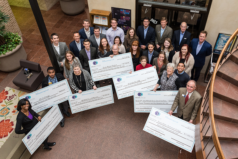 Members of the Fall 2016 Strategic Philanthropy course present checks to local nonprofit organizations.