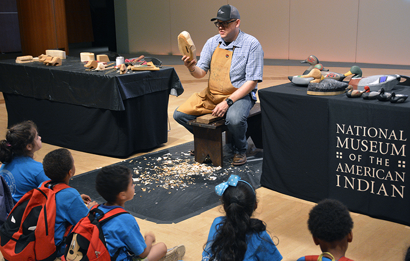 Young visitors from a New York City area summer camp watch as Joshua Hinson creates a duck decoy during a live exhibition at the National Museum of the American Indian.