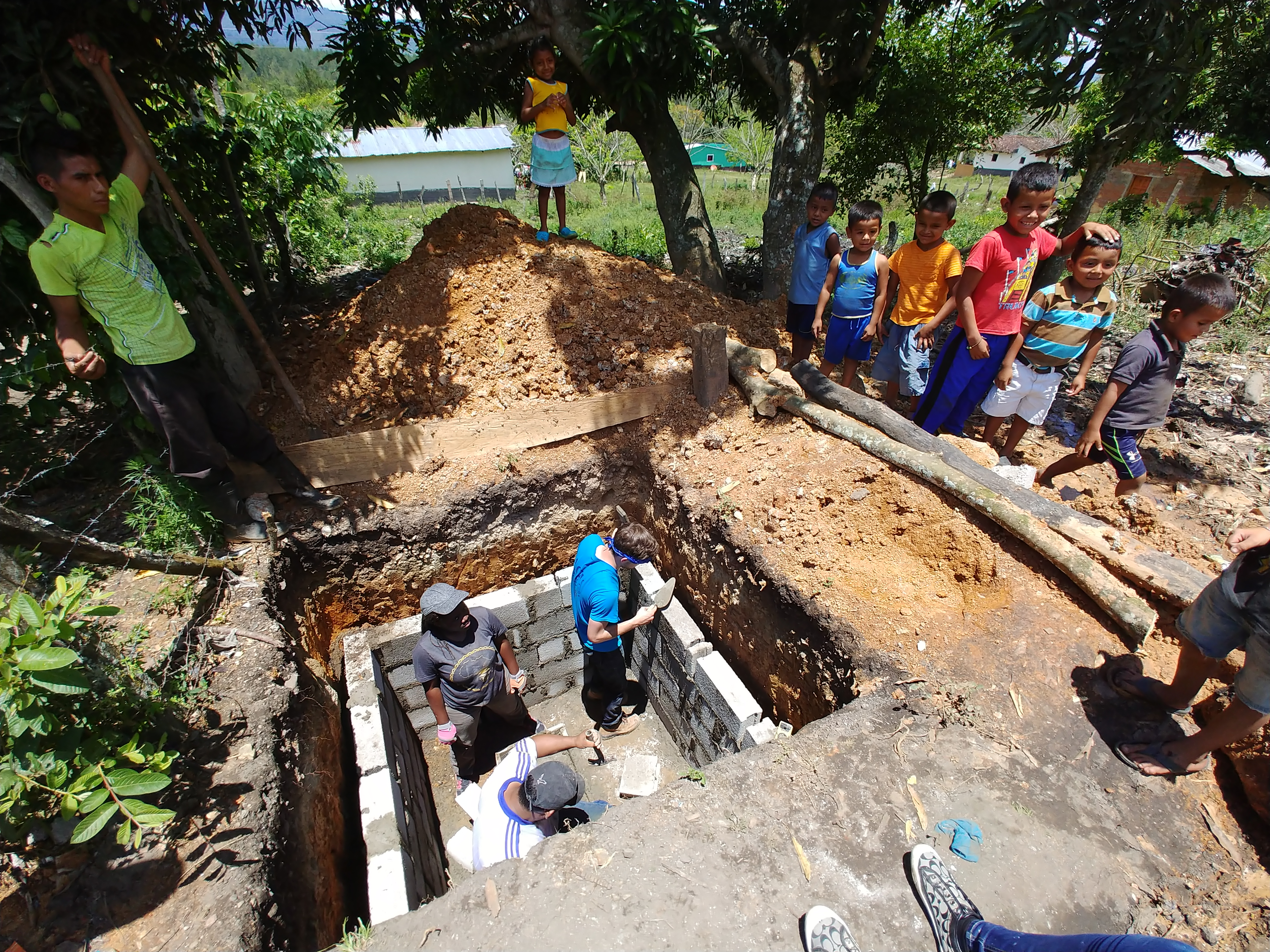 Children in the village of Linares, Honduras, watch ACU engineering and physics students construct latrines they designed as a class project.