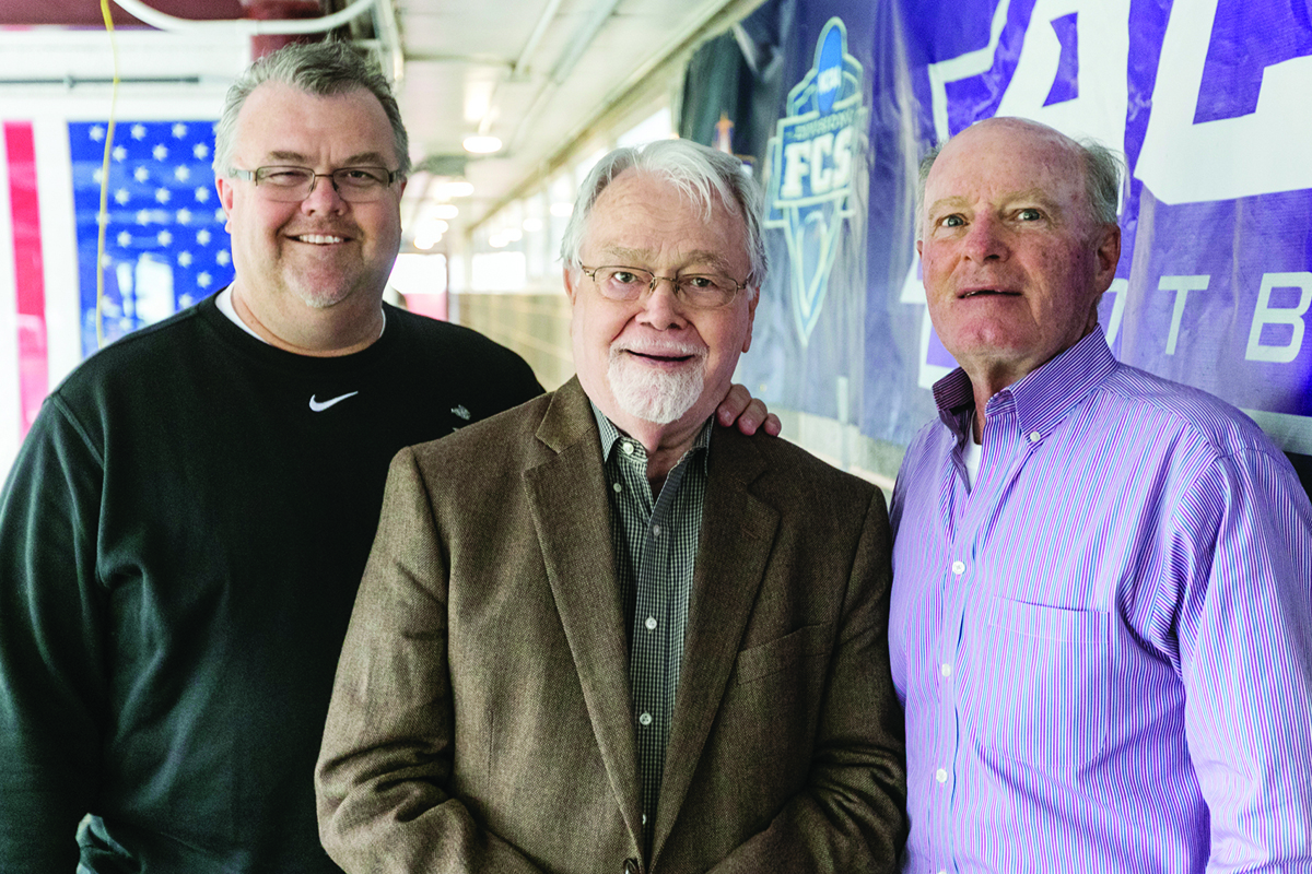 Fleming (left), Dr. Charlie Marler (center) and Garner Roberts (right) pose together in the press box at Shotwell Stadium in 2016. Marler ('55) and Roberts ('70) – former ACU sports information directors like Fleming – are two of the contributing writers to his new book on ACU football history.