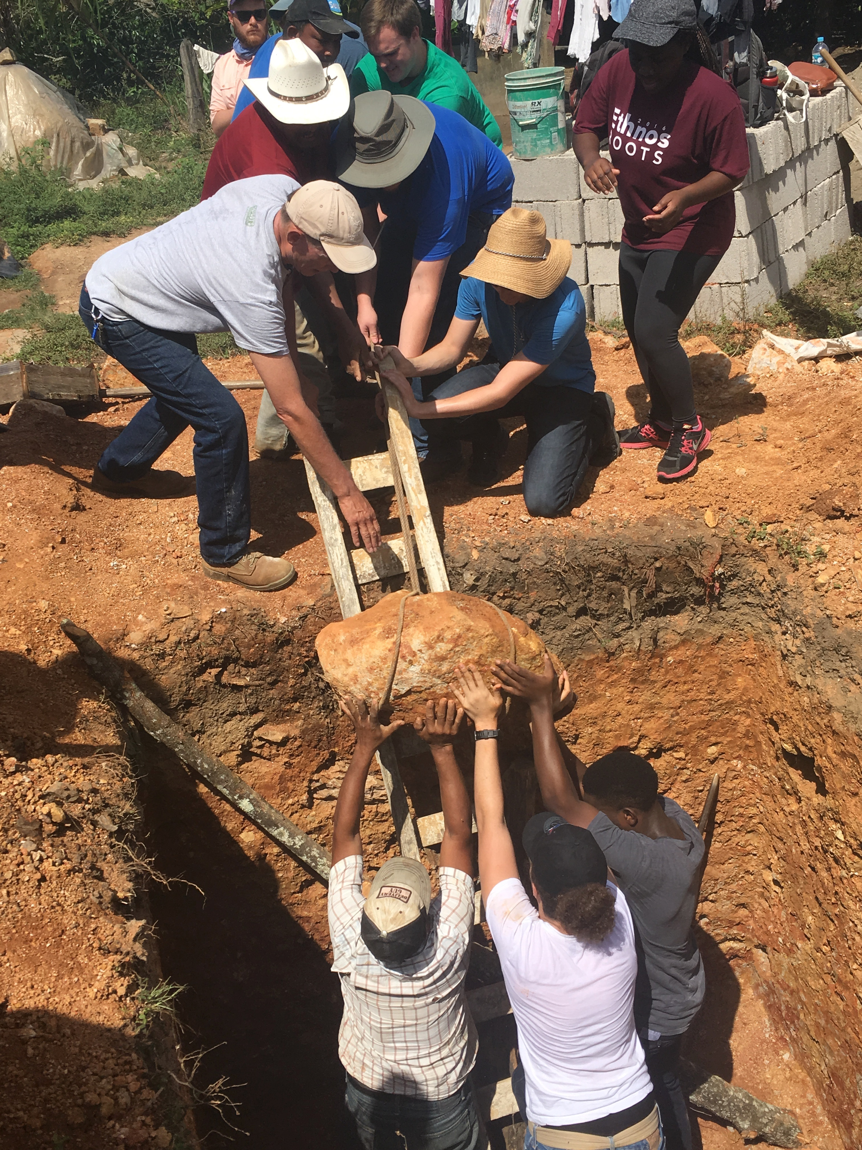 """ACU engineering and physics students work with a family in Linares to """"engineer"""" a solution to get a large rock out of the latrine pit before beginning construction."""