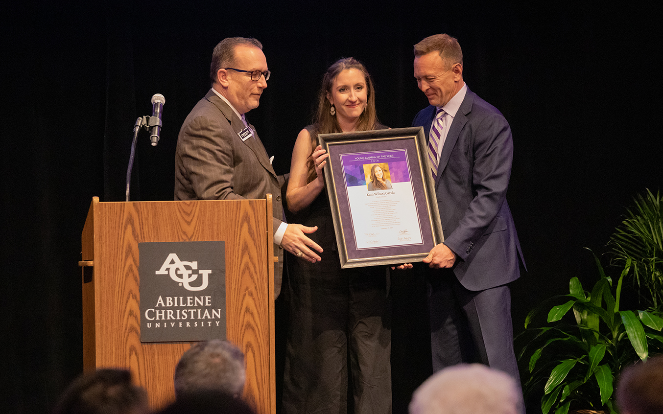 Wilson García receives her Young Alumna of the Year certificate at the Alumni Day luncheon Feb. 17, 2019, from Craig Fisher ('92) (left), assistant vice president of alumni and university relations, and Dr. Phil Schubert ('91), president.