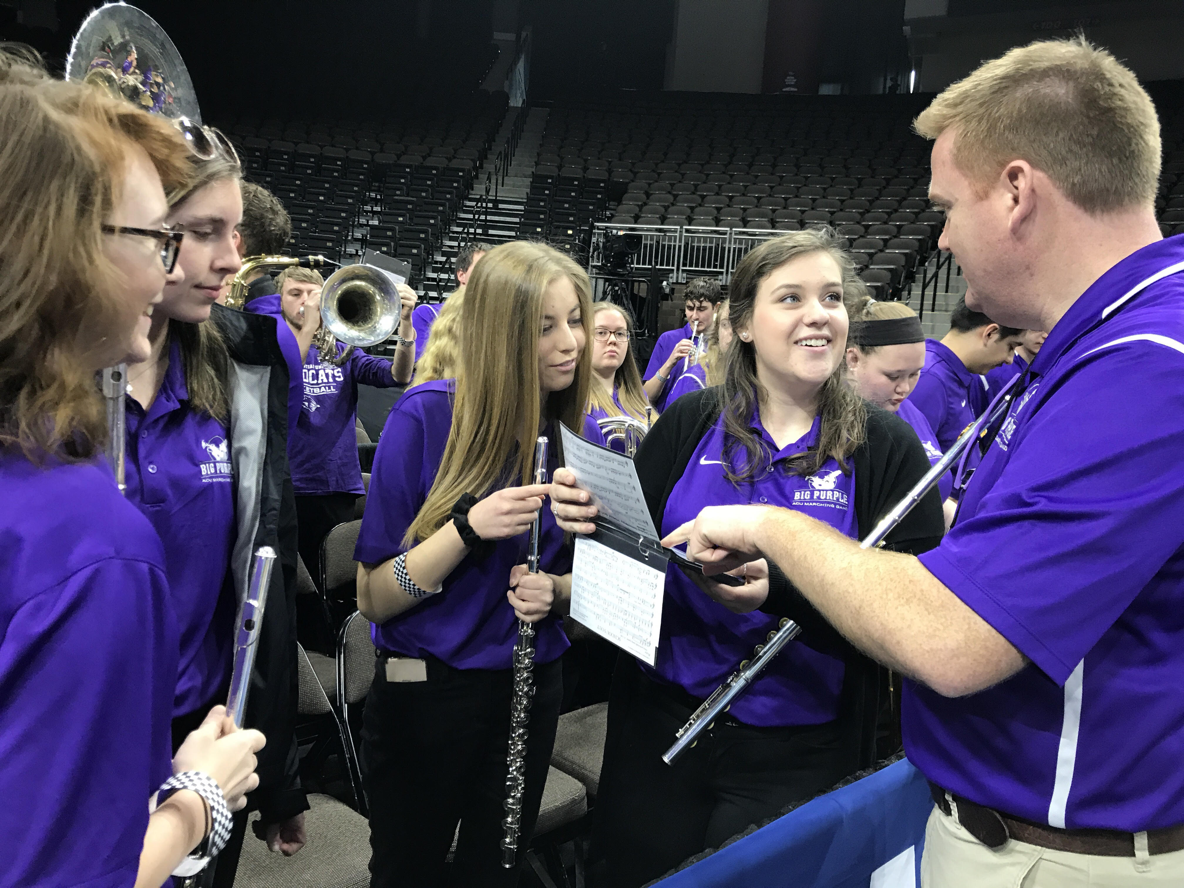 At a practice session in the arena on Wednesday in Jacksonville, (from left) Emily Tiras, Faith Parsons, Bailey McCall and Alli Mae Bulkley discuss music selections for the upcoming game with Dr. Brandon Houghtalen (right).