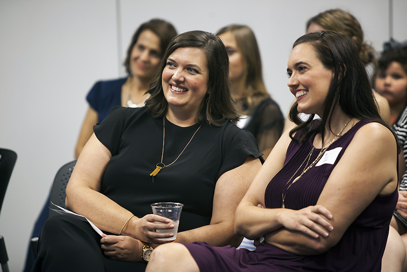 Katie Coldwell ('00), left, and her sister, Sarah Coldwell, listen as Katie is honored with a 2019 Distinguished Alumni Citation.