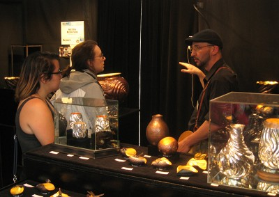Ashley Smith and Kaitlyn Brown visit with a jewelry/metal artist at the Fort Worth Arts Festival.