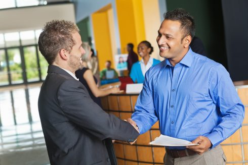 Professional man meeting employee with resume at job fair event