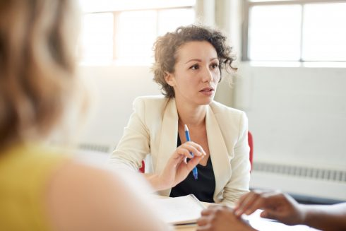 Candid picture of a female boss and business team collaborating.