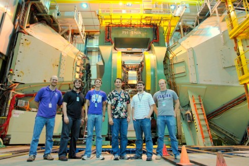 ACU students and professors standing in front of the PHENIX detector at RHIC.