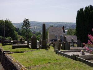 View from St. Patrick's churchyard across a valley to green hills.