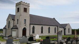 Grey stone church with square corner tower entrance, surrounded by church graveyard.