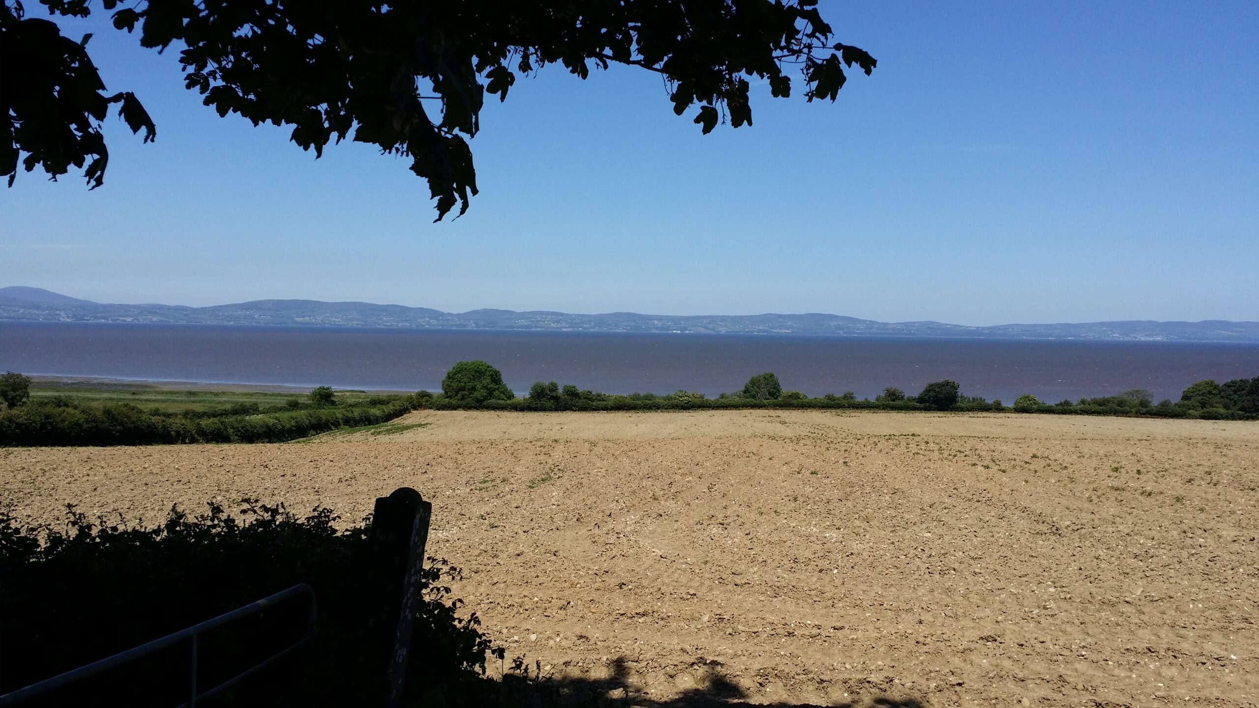 Lough Foyle runs from left to right across the middle of the photo with the hills of Donegal on the other shore and a plowed field in Northern Ireland in the foreground.