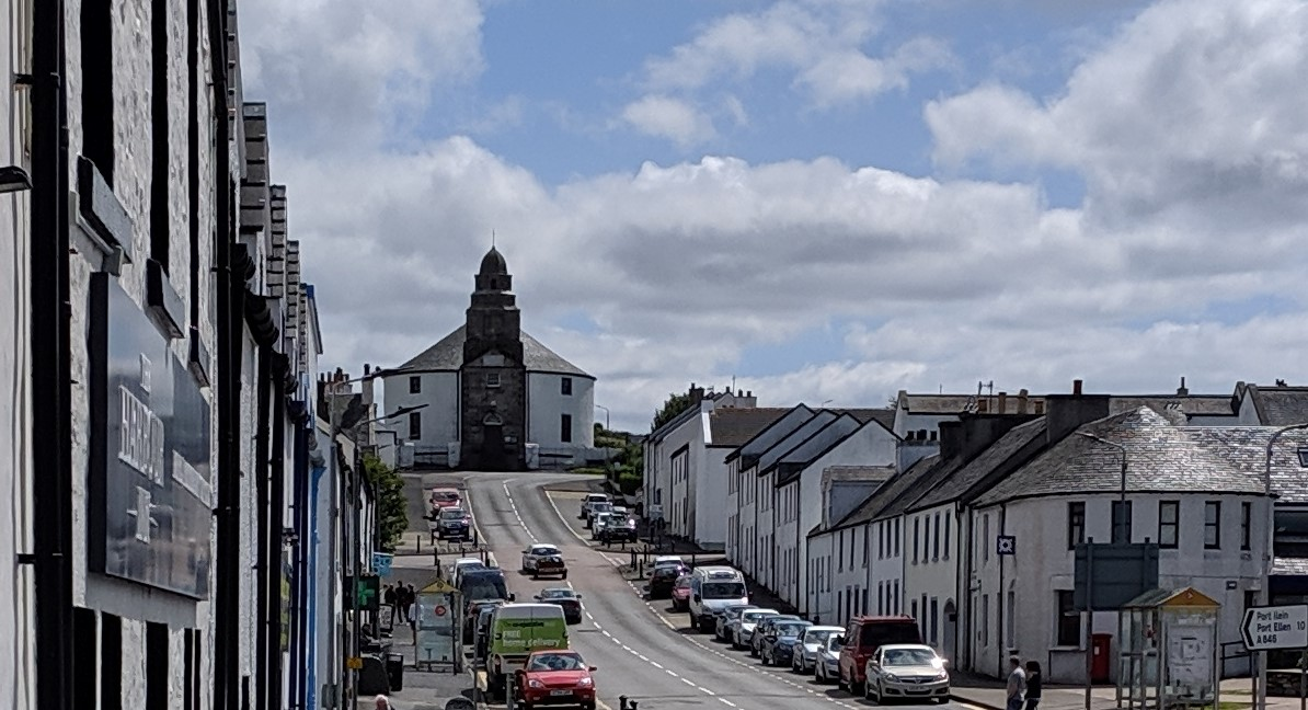 A steep town road lined with houses rises to a white round church with a stone steeple facing the street. Kilarrow Parish Church, 1767
