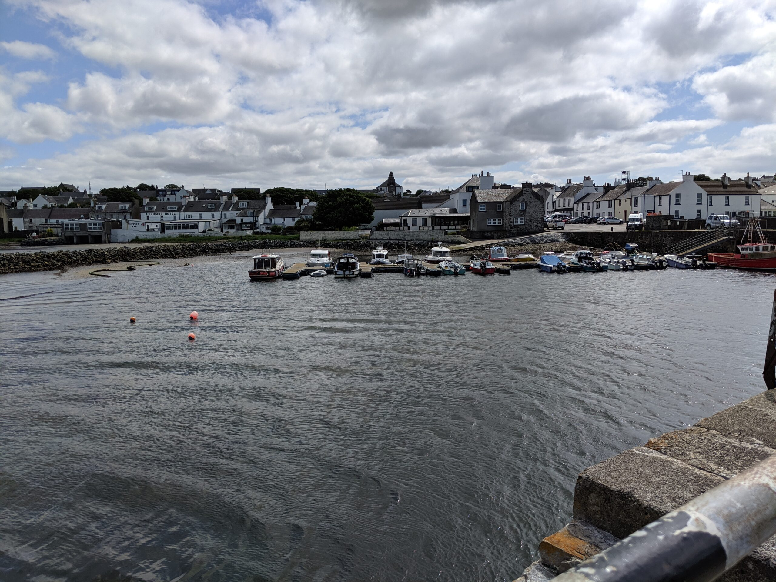 The harbor of the village of Bowmore, Islay, with the round Kilarrow Parish Church rising above the houses clustered by the waterside.