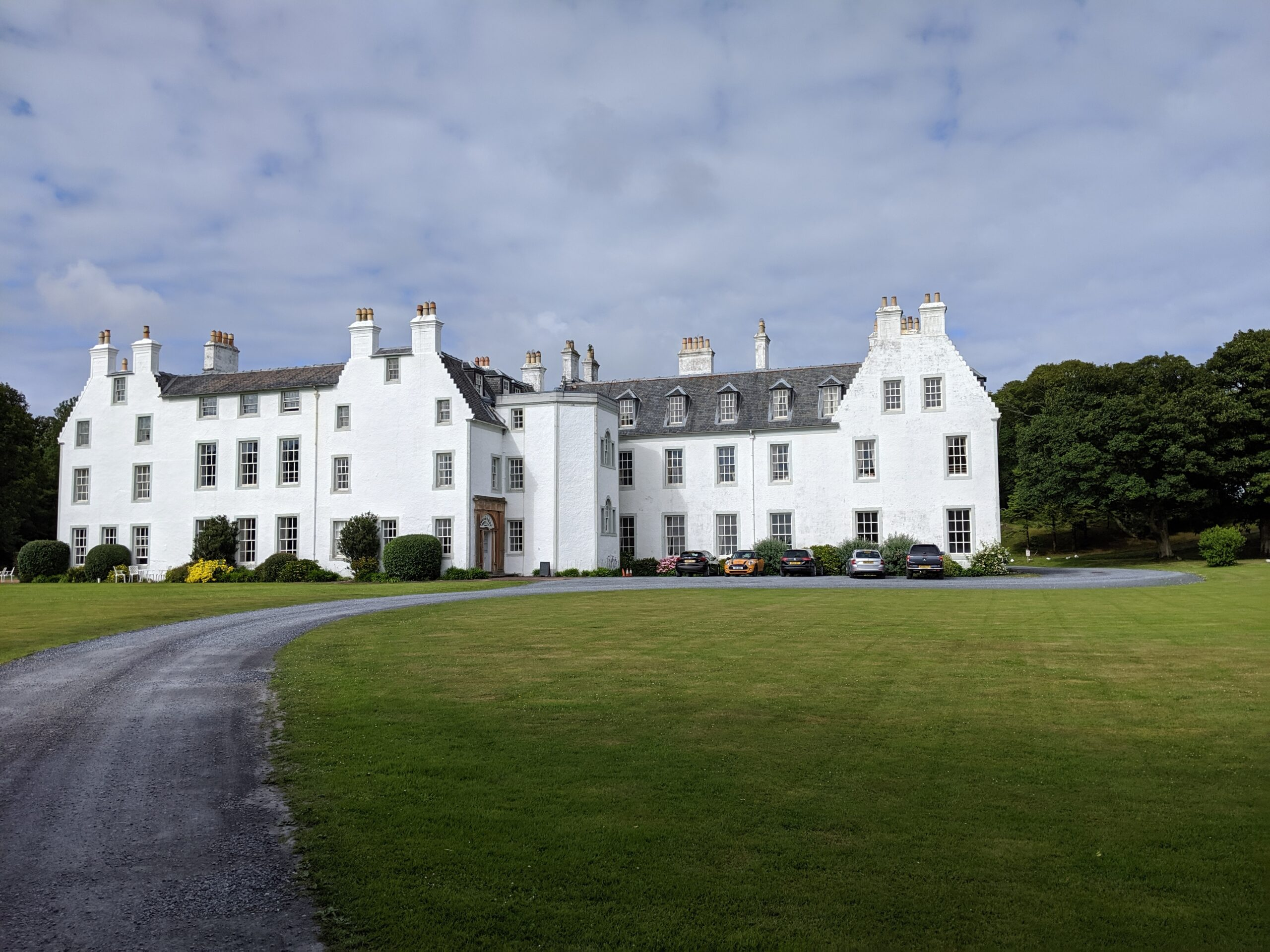 White mansion with more than a dozen chimneys, two storeys, and attic windows below the grey roof. Photograph across a wide green lawn and lane. The main entrance in the center faces to the east side.