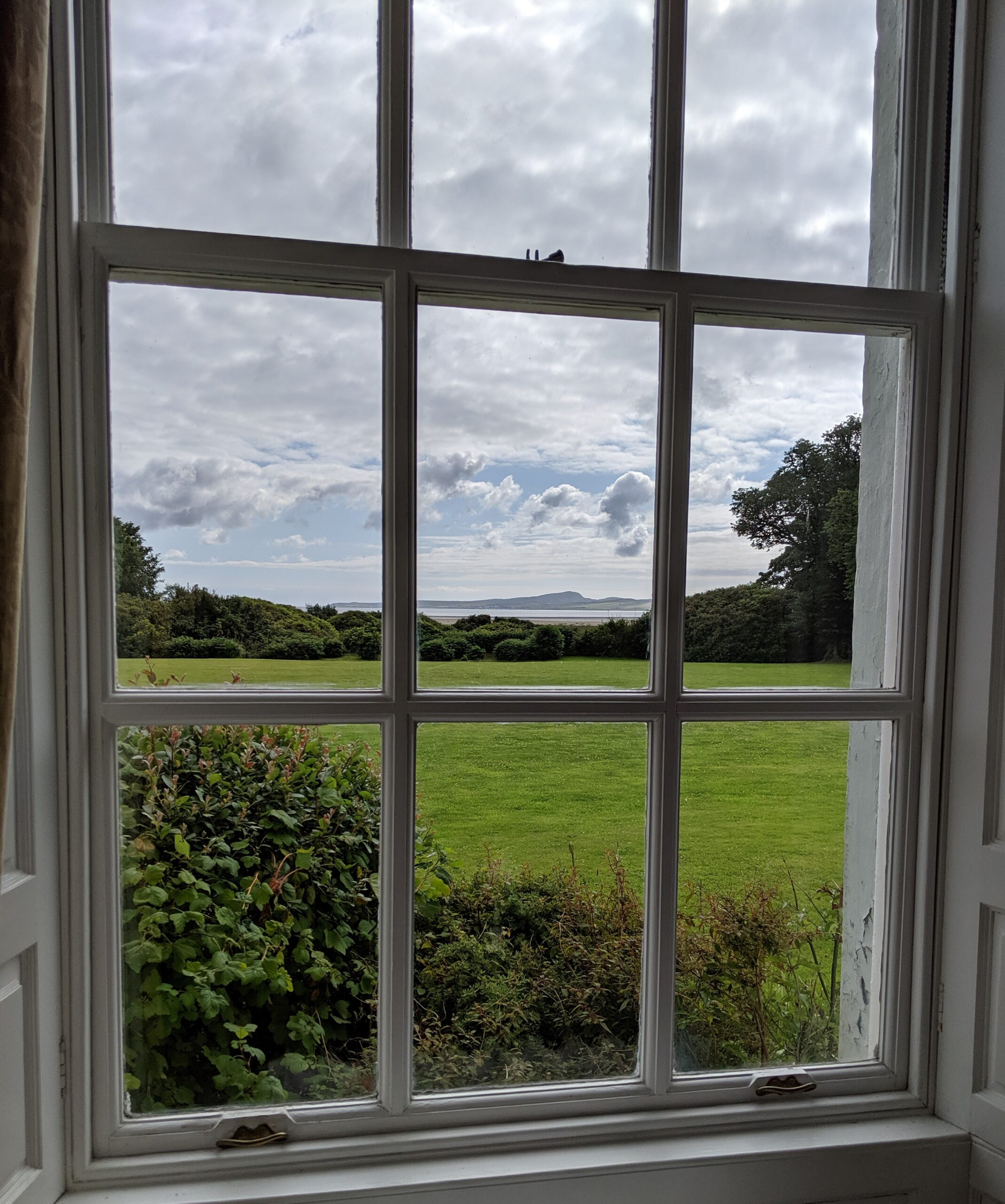 View from Islay House through nine panes of glass south across the estate's lawn toward Lochindaal Bay and the moors of Gearach.