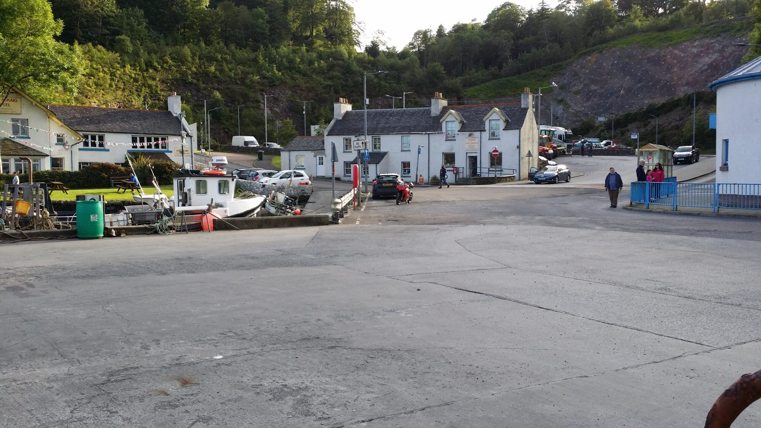 Village of Port Askaig founded 1767. View from dockside toward hotel at left, post office and shop at center, and dock buildings at right.