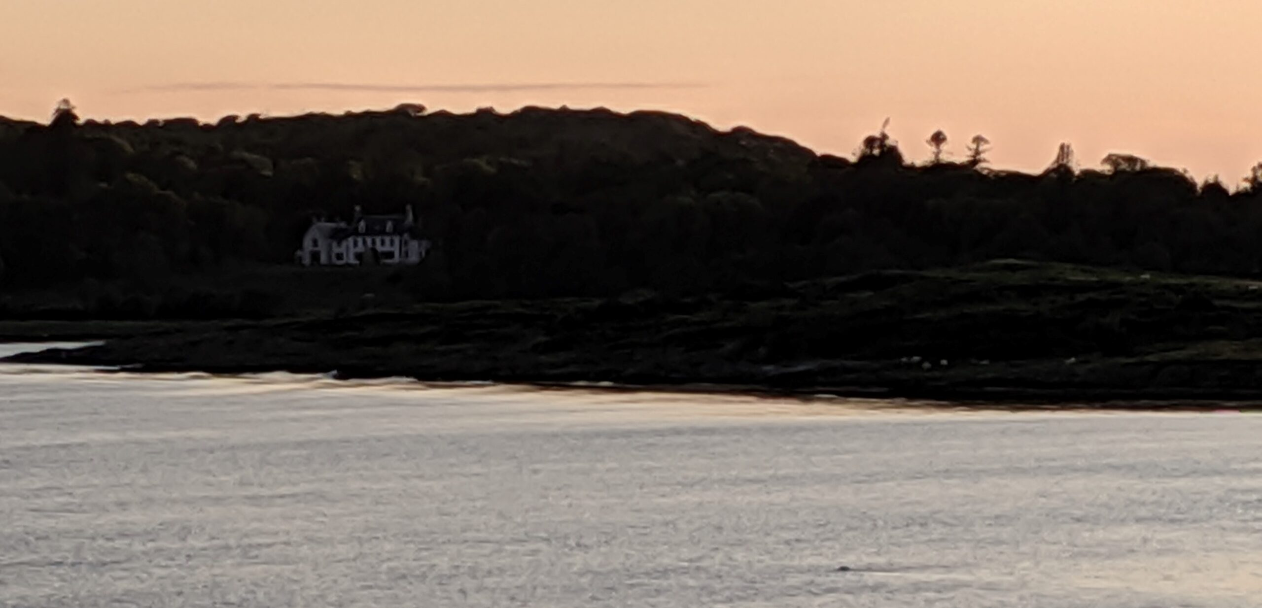 Laird Campbells white home on a dark shore with sunset colors in the sky