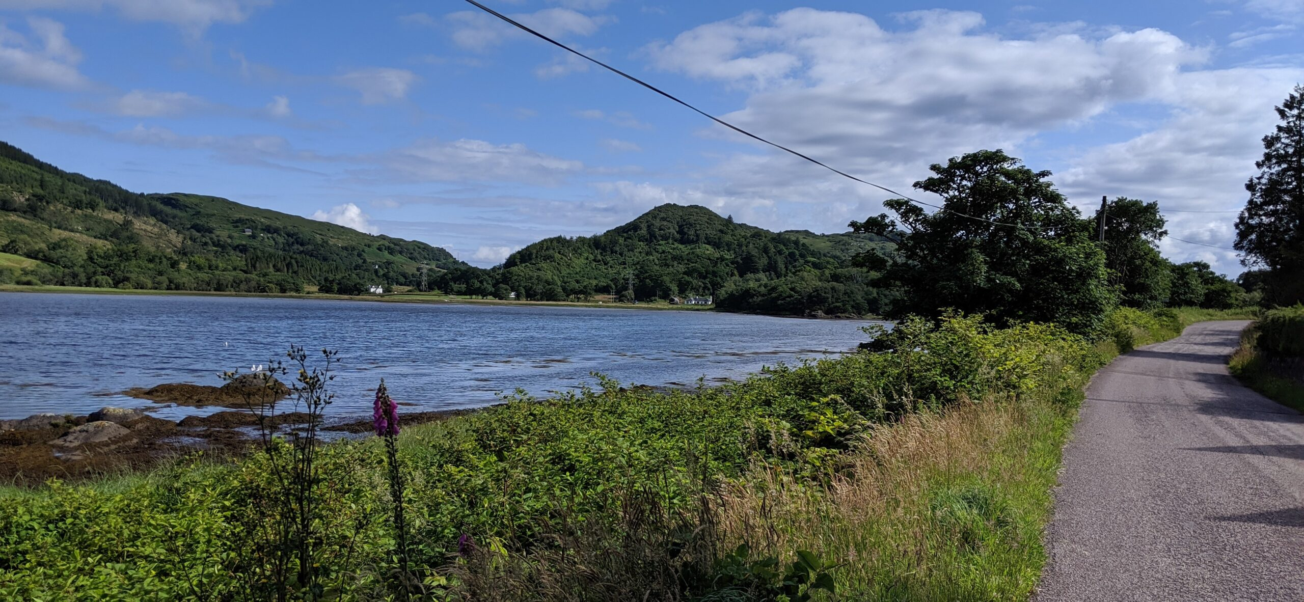 The waters of West Loch Tarbert at left end at a hill. To the right, a road winds toward the hill and around it.