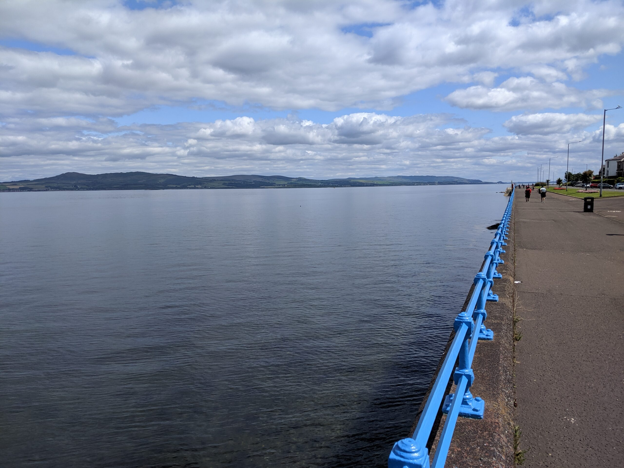The port of Greenock lies on the Firth of the Clyde River. A wide river with a blue protective rail and pavement on the right, and mountains across the river.