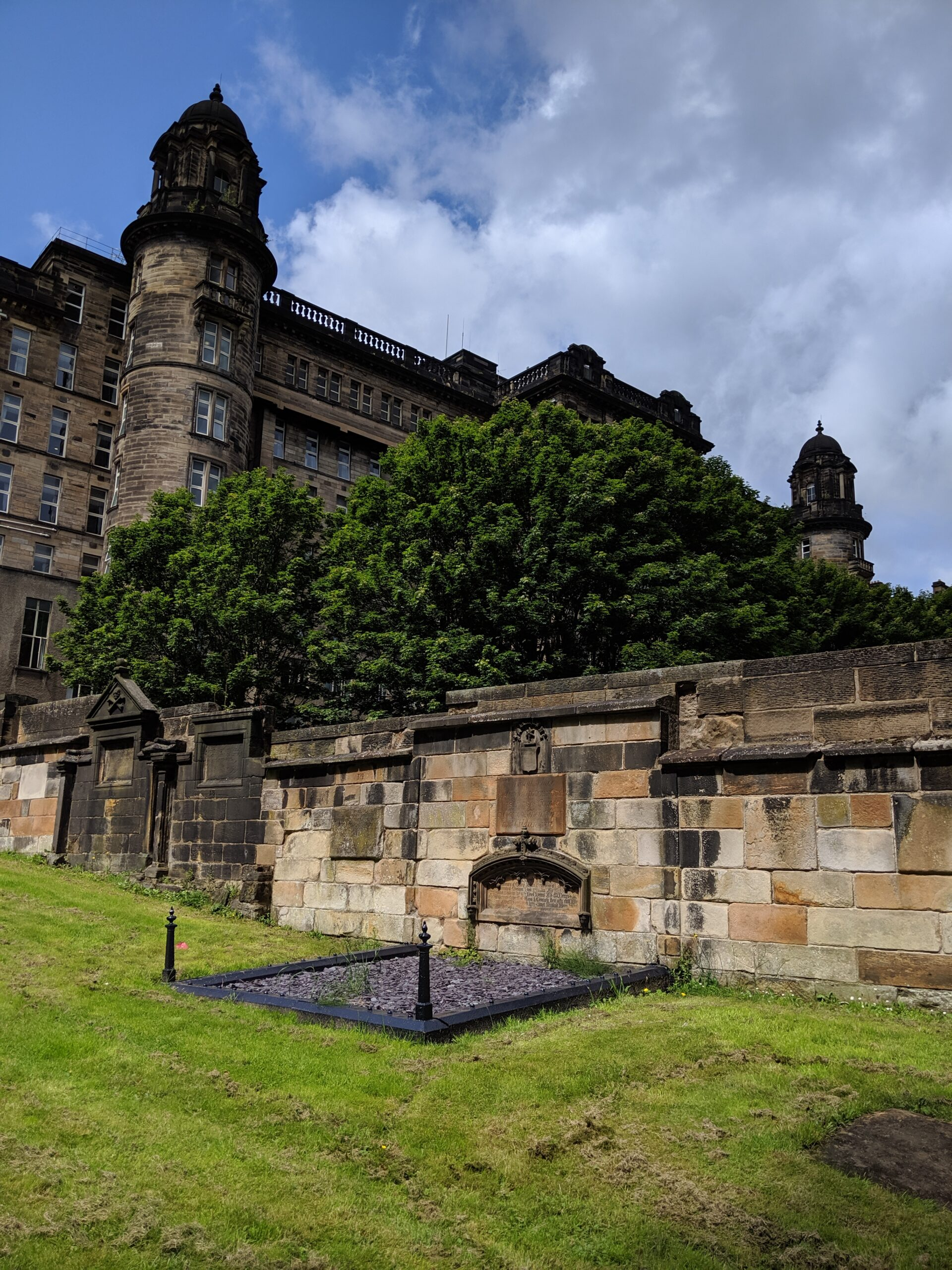 Large multistory stone building, with a stone wall and a burial plot in the foreground