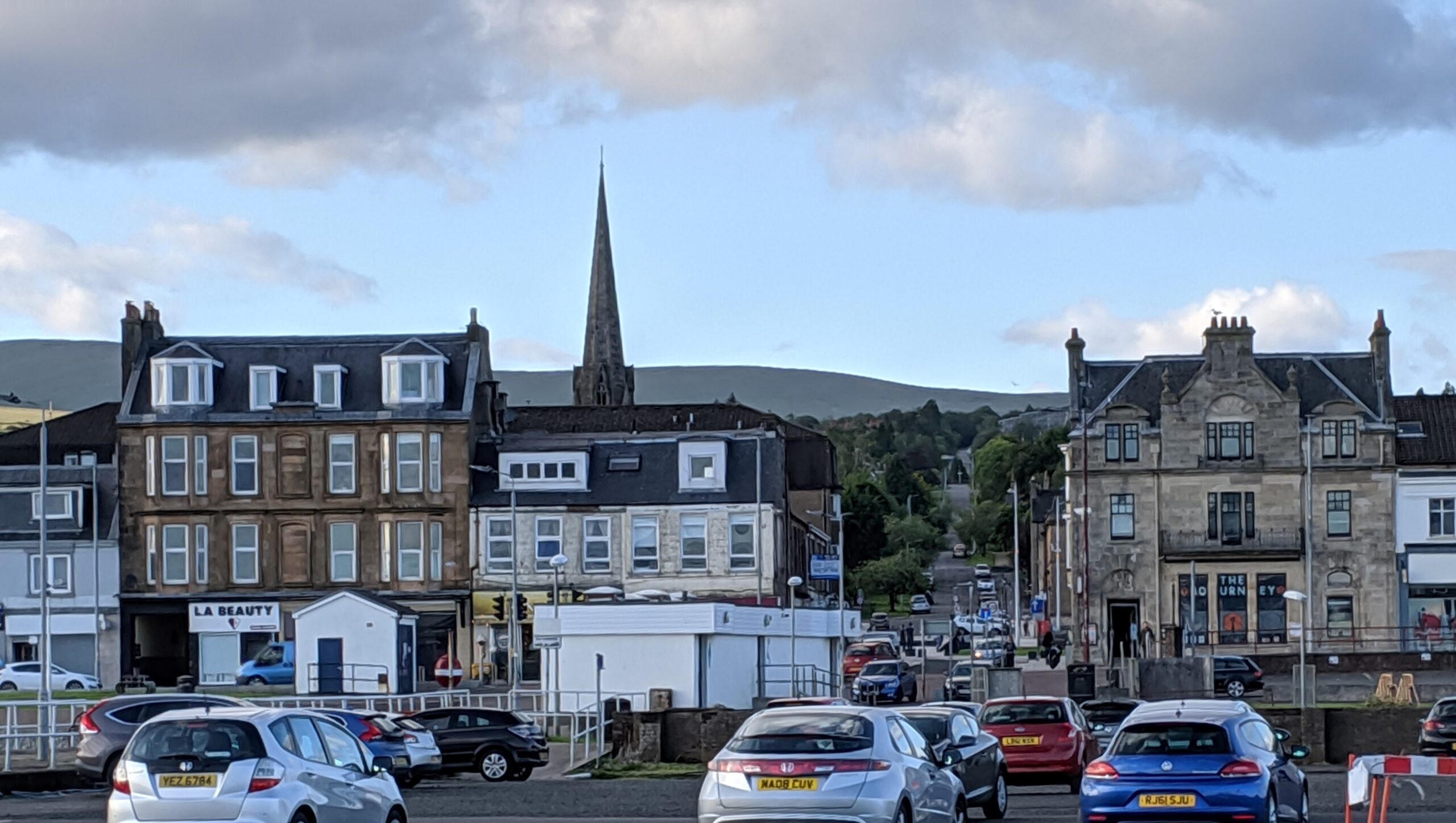 Old three- and four-story buildings face the wharf at Helensburgh, with the green hills of the Scottish highlands rising behind.