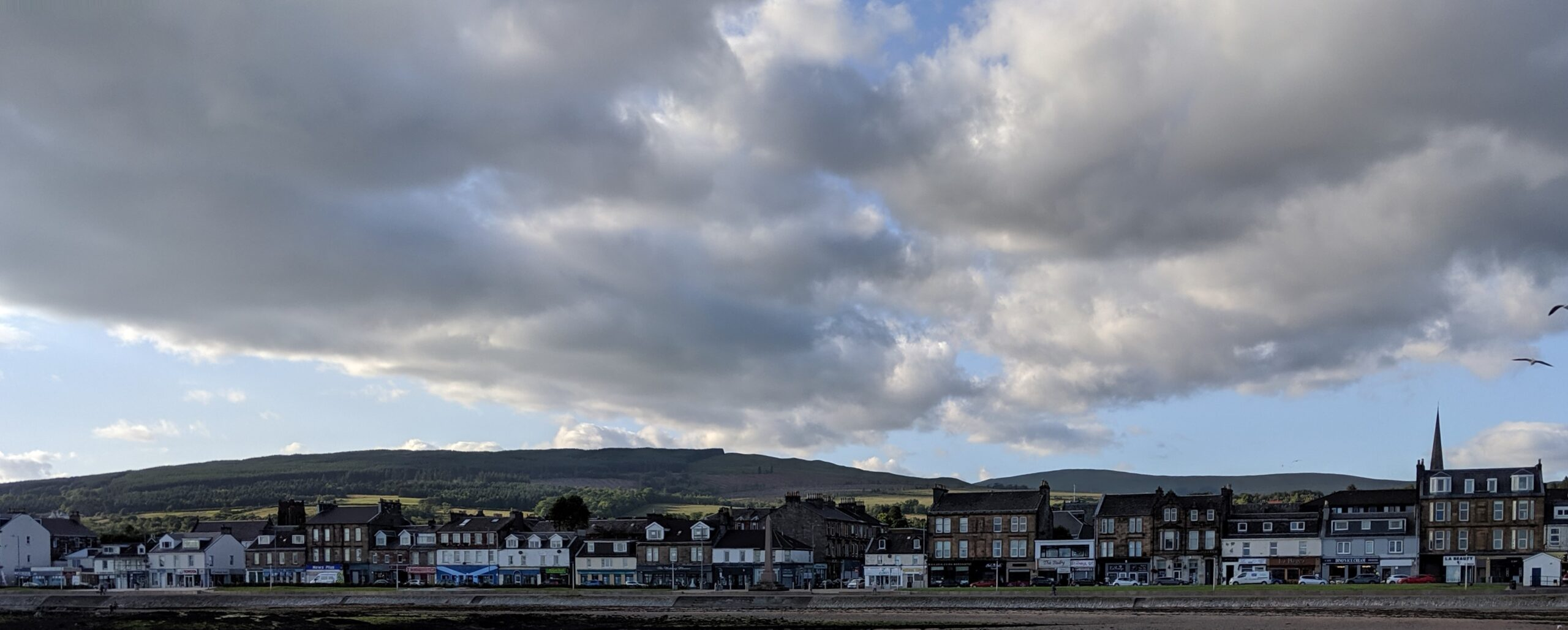 Panoramic view of the resort town from a distance between the Firth of Clyde and the Scottish Highlands rising behind the town.
